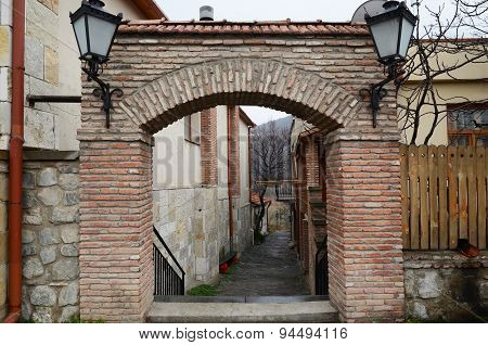 Brick arch with lanterns and narrow small street in the city of Mtskheta. Georgia