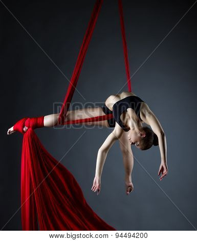 Graceful acrobat posing while doing trick
