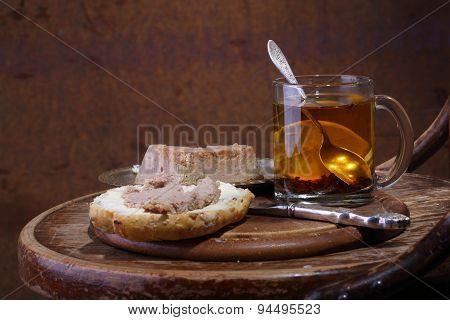 Sandwich With Paste And Tea With A Lemon In A Transparent Mug On A Wooden Table