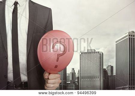 Businessman holding balloon in hand on cityscape background