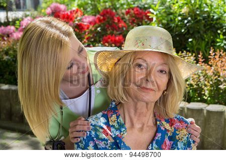 Portrait Of Senior Woman With Nurse Outdoors