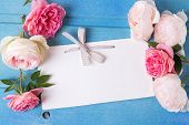 stock photo of blue rose  - Sweet pastel roses and empty tag on blue wooden background - JPG