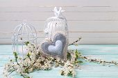 foto of caged  - Background with white spring blossom of trees decorative heart and candles in bird cages on turquoise wooden planks - JPG