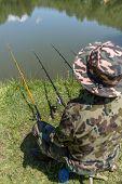 stock photo of rod  - Fisherman sitting near lake with fishing rods - JPG