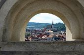 stock photo of red roof  - Red tile roofs and buildings of Chesky Krumlov viewed through stone arch - JPG