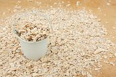 picture of bucket  - White bucket with oat flakes on the wooden floor as a background - JPG