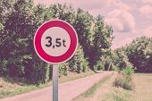 pic of restriction  - Traffic sign of 35 tons weigh restriction on a rural road background - JPG