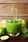 pic of mint-green  - Glass of green healthy juice with mint and fruits on wooden background - JPG