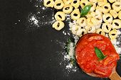 image of ladle  - raw tortellini pasta and ladle with sauce on black surface - JPG