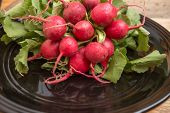 picture of radish  - Red radishes in black bowl on weathered wood background - JPG