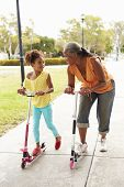 picture of granddaughter  - Grandmother And Granddaughter Riding Scooters In Park - JPG