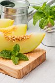 picture of muskmelon  - Juicy honeydew melon on a wooden table background - JPG