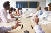 image of pov  - Point Of View Shot Of Businesspeople Around Boardroom Table - JPG