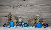 stock photo of nutcracker  - Wooden christmas background in grey with blue turquoise nutcrackers - JPG