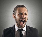 stock photo of screaming  - Portrait of an angry furious businessman screaming - JPG