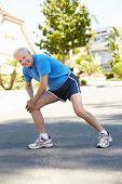 foto of running-late  - Elderly man warming up for run - JPG