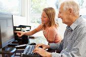 image of granddaughters  - Senior man and granddaughter using computer - JPG