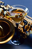 stock photo of saxophones  - saxophone and martini with green olives focus on foreground  - JPG