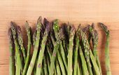 stock photo of immune  - Fresh green asparagus on wooden surface concept of healthy food nutrition and strengthening immunity - JPG