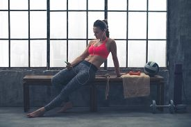 stock photo of sitting a bench  - A fit buff muscular woman is sitting relaxed on a wooden bench in her local loft gym - JPG