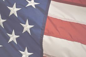 stock photo of emblem  - Faded patriotic holiday background of the american flag closeup - JPG