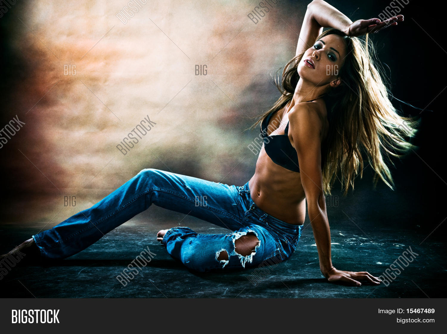 young sexy woman in blue jeans and brassiere dancing on the floor ...