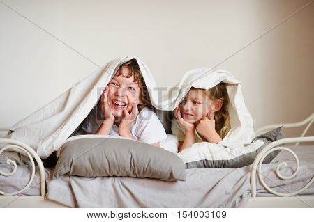 Little brother and sister made a play on the bed in the bedroom. Children look out from under the blanket laughing.