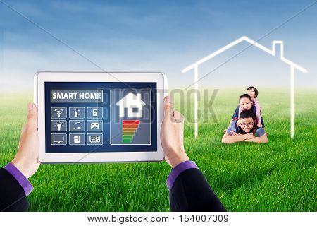 Hands holding a digital tablet with smart home controller applications on the screen. Shot with happy children and their father lying under a house symbol