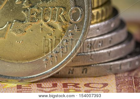 Euro money: Macro view of euro coin and bill with the word Euro focused. Suitable for financial, monetary, euro or European Union concepts and ideas