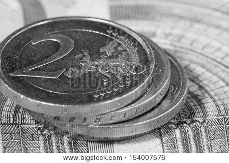 Euro money: Macro view of euro coin and bill with the word Euro focused. Black and white image. Suitable for financial, monetary, euro or European Union concepts and ideas