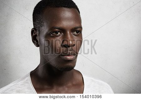 Close Up View Of Handsome Dark-skinned Male Looking Serious And Thoughtful On Blank Studio Wall Back
