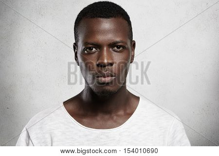Close Up Portrait Of Good-looking Serious African Man With Healthy Clean Skin Wearing White Casual T