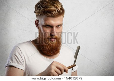 Good-looking Professional Barber With Thick Red Beard And Mustache, Holding Straight Razor. Young Ca
