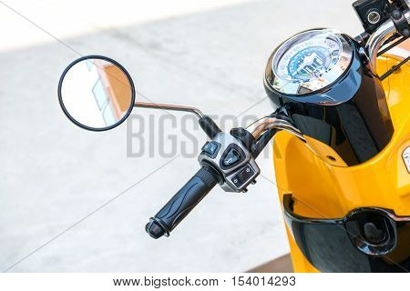 Closeup to handlespeedometer and rear view mirror of the motorcycle.