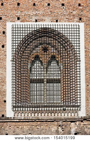 Detail of an ancient window with grating in wrought iron of the Sforza Castle XV century (Castello Sforzesco) in Milano Lombardy Italy