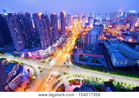 A bird's-eye view of the city's modern architectural high-rise and busy road night views.