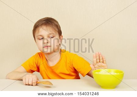 Little cute boy refuses to eat a cereal