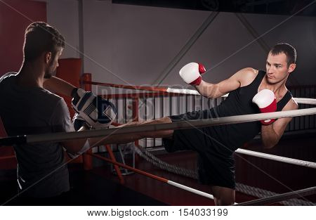 Making gold. Young serious man practicing kick boxing hook on ring together with his personal trainer.