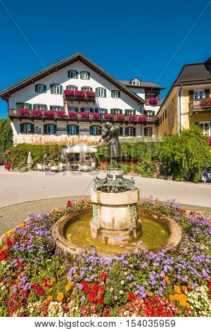 St. Gilgen Austria - August 24 2016: Statue of young Wolfgang Amadeus Mozart and a famous hotel