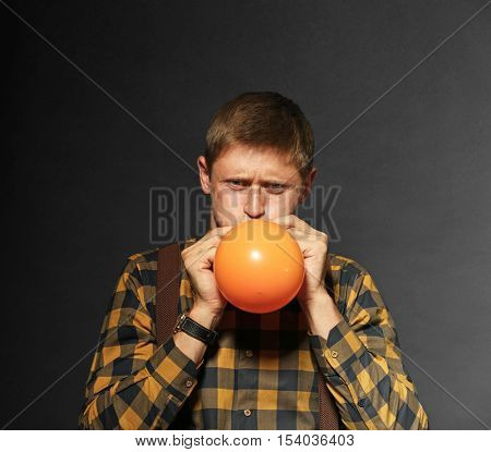 Young man puffing balloon on dark background