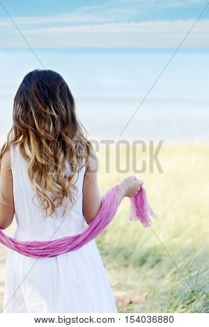 back of young girl at beach pink scarf