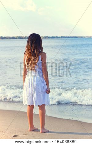young girl in white dress on beach