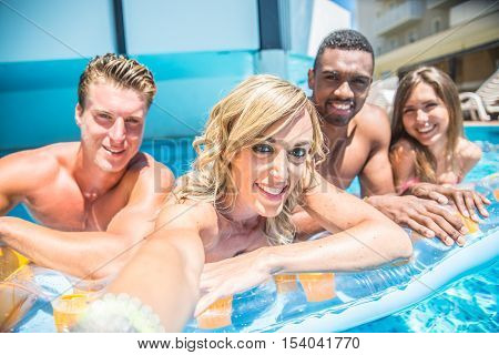 Group of best friends taking selfie at the swimming pool with airbed - Summer holidays tourists enjoy sunbathing in a resort's pool
