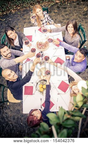 Group of friends at restaurant outdoors toasting wine glasses - People having dinner in a home garden