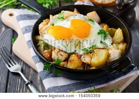 Hearty breakfast. Hash brown potatoes chicken onion parsley oregano and a fried egg in a frying pan on the old wooden background. Selective focus.