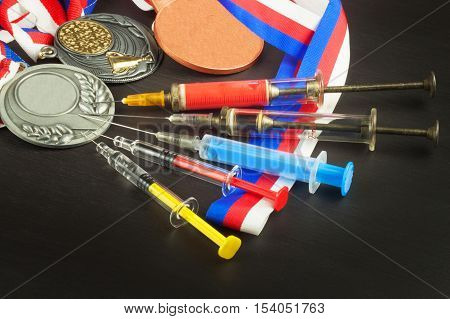 Syringe and medals. Doping in sport. Abuse of anabolic steroids for sports. Anabolic steroids spilled on a wooden table. Fraud in sports. Doping athletes.