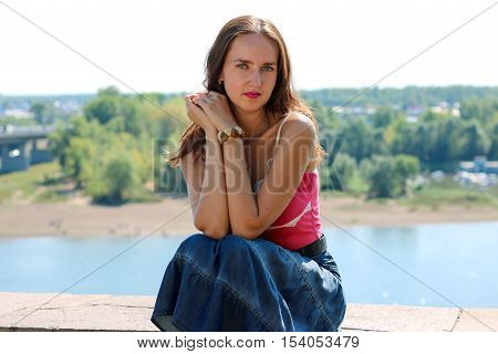 French girl with denim skirt sitting on a background of the river.
