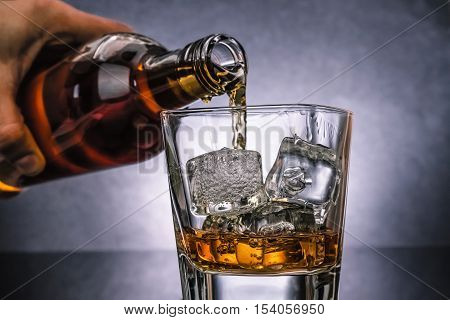 Barman Pouring Whiskey With Ice Cubes In Glass On Black Background, Cold Atmosphere