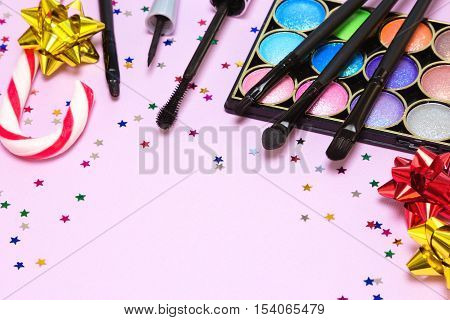 Makeup for festive party. Bright color glitter eyeshadow, mascara, liquid eyeliner, lip gloss, applicator, brushes with candy cane, gift wrap bows and confetti. Shallow depth of field, copy space