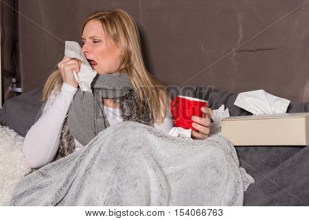 Attractive woman with cold sneeze in a handkerchief